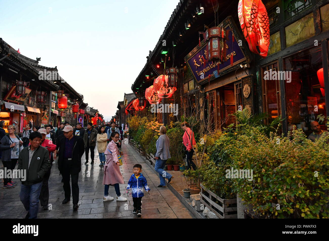 (181017) -- PINGYAO, Oct. 17, 2018 (Xinhua) -- Tourists walk on an old street of the ancient walled city of Pingyao in Jinzhong, north China's Shanxi Province, on Oct. 16, 2018. The ancient walled city of Pingyao was built in the 14th century, and was named a UNESCO world heritage in 1997, as 'an exceptionally well-preserved example of a traditional Han Chinese city.' The city boomed in the 19th century as China's financial center, as Shanxi merchants expanded their businesses across the country. Now, the well-preserved compounds of these affluent merchants and some emerging modern elements li - Stock Image