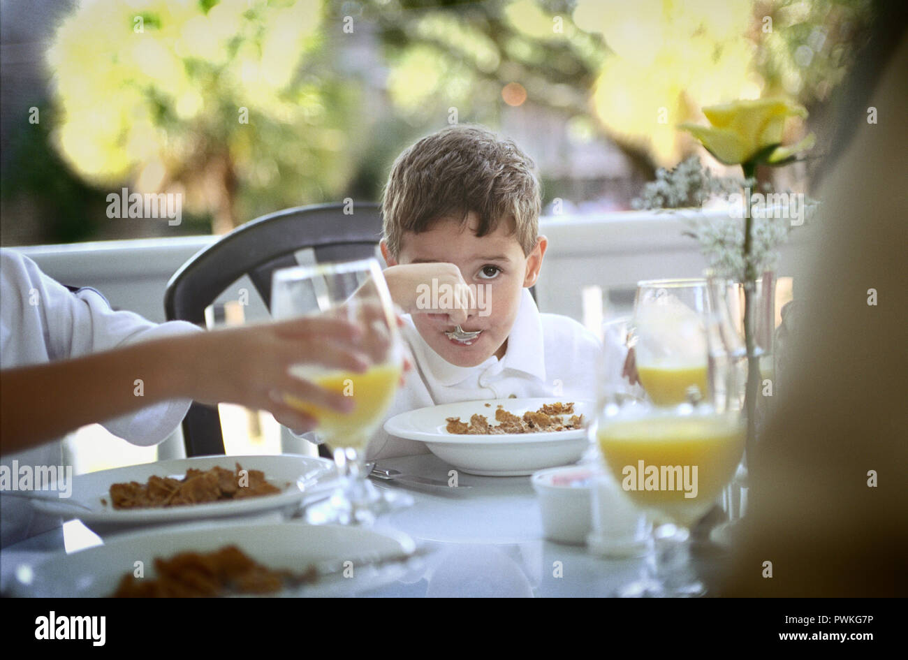 A small boy eating his breakfast at a table. - Stock Image