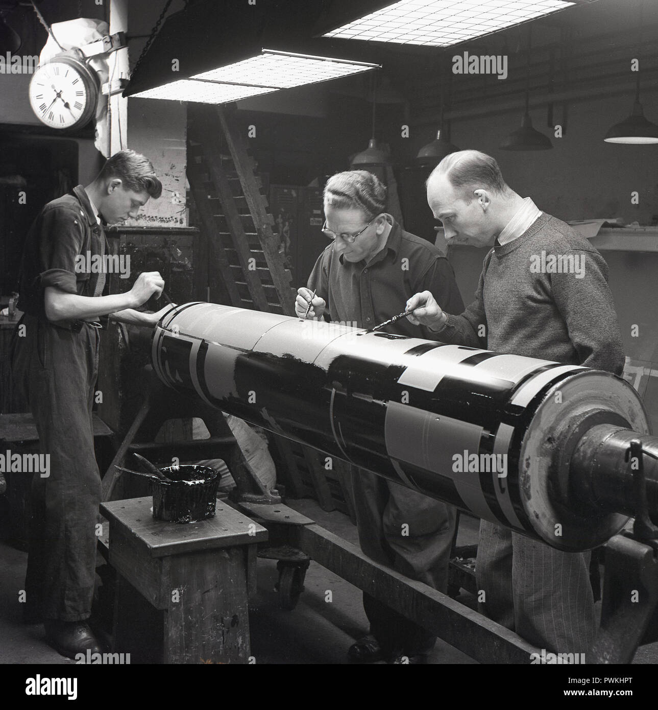 1050s, HWV, magazine printers, two male workers and young male apprentice painting images with black ink onto a metal cyclinder before printing, Engalnd, UK> - Stock Image