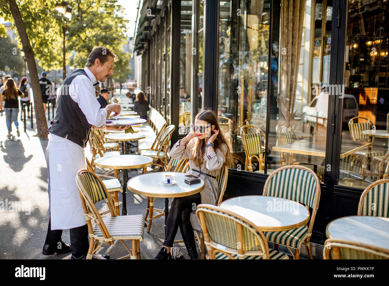 PARIS, FRANCE - August 31, 2018: Waiter serving coffee to a young woman client sitting at the traditional french cafe outdoors in Paris - Stock Image