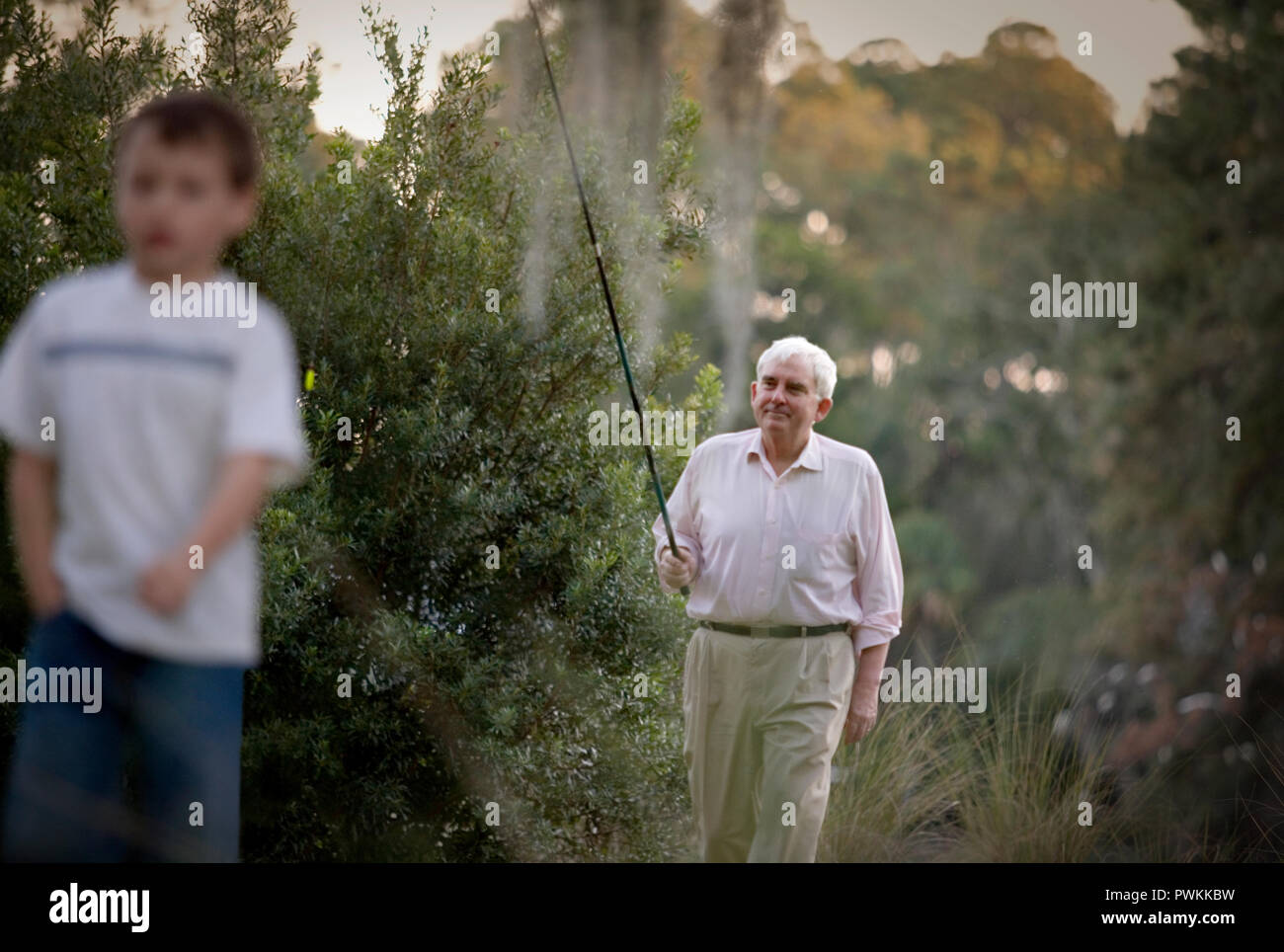 Senior adult man walking through scrubland carrying a fishing rod with his young grandson. - Stock Image