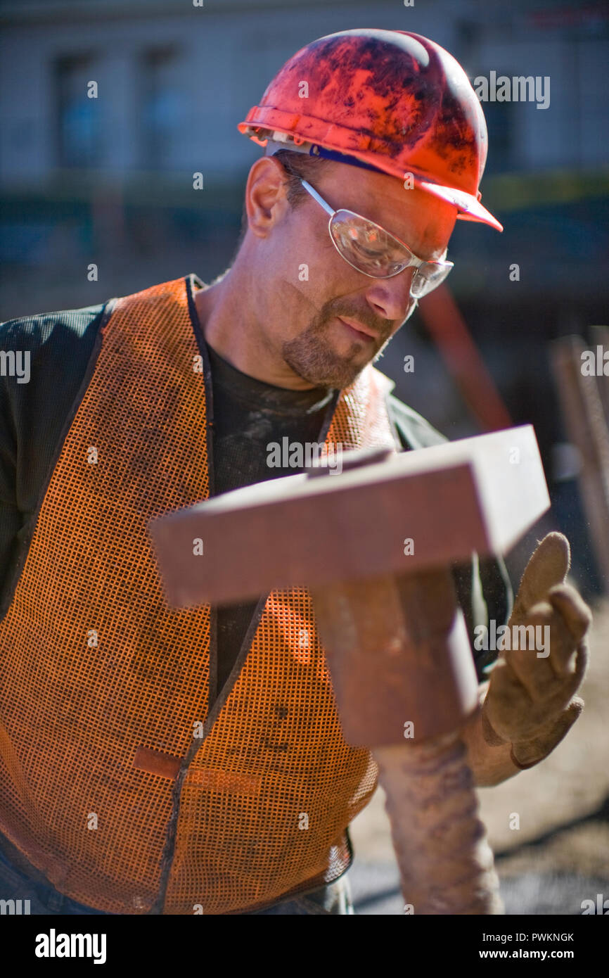Dirty mid-adult construction worker wearing a helmet and safety glasses while working on a construction site. - Stock Image
