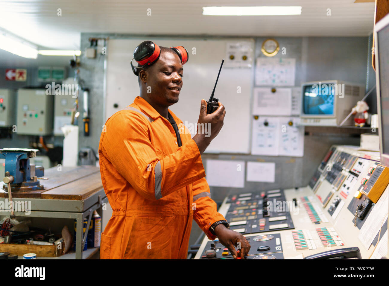 Marine engineer officer working in engine room - Stock Image