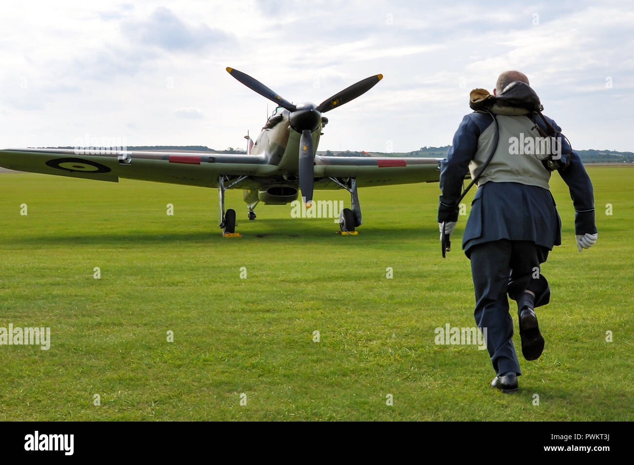 Battle of Britain scramble recreation. RAF Royal Air Force Second World War pilot re-enactor runs towards Hawker Hurricane fighter plane - Stock Image