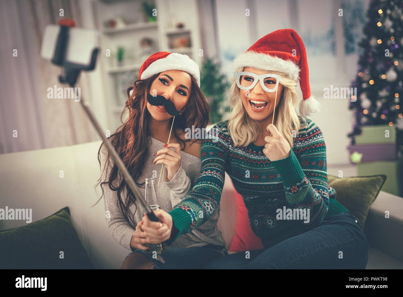 Funny female friends having nice time taking selfie in an apartment. - Stock Image
