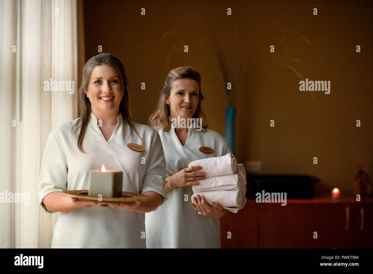 Portrait of two smiling middle-aged massage therapists at a health spa. Stock Photo