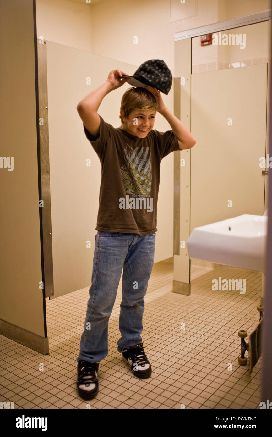 Smiling young boy standing in a public bathroom. Stock Photo