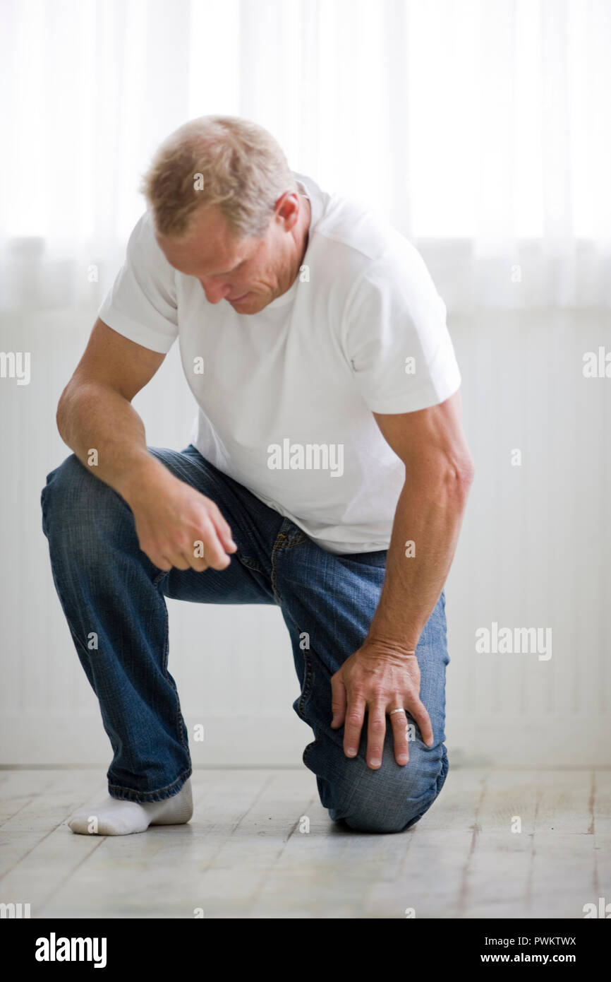 Man kneeling on floor and looking down Stock Photo