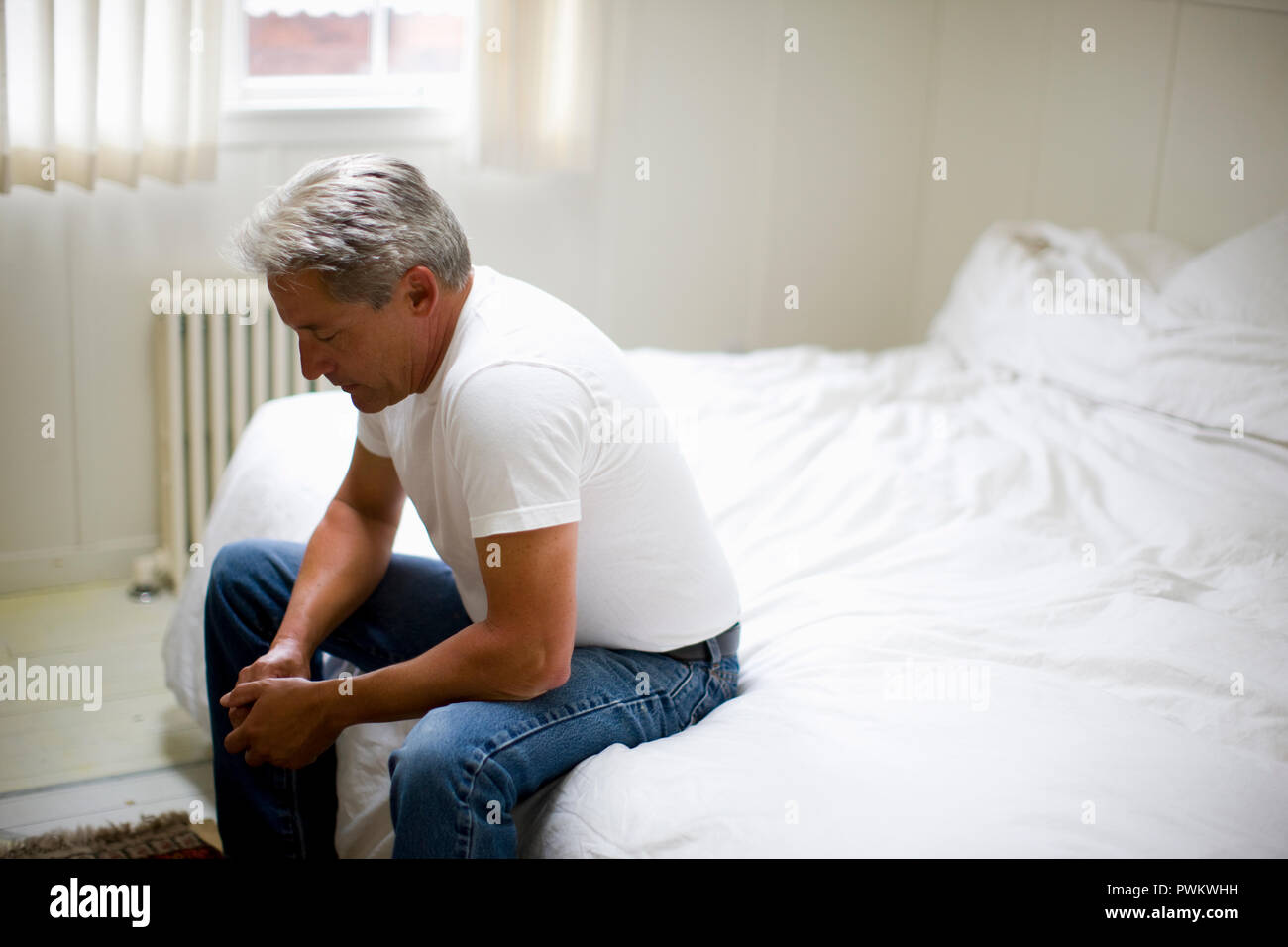 28502609745 Contemplative mature man sitting on the edge of the bed in his bedroom.