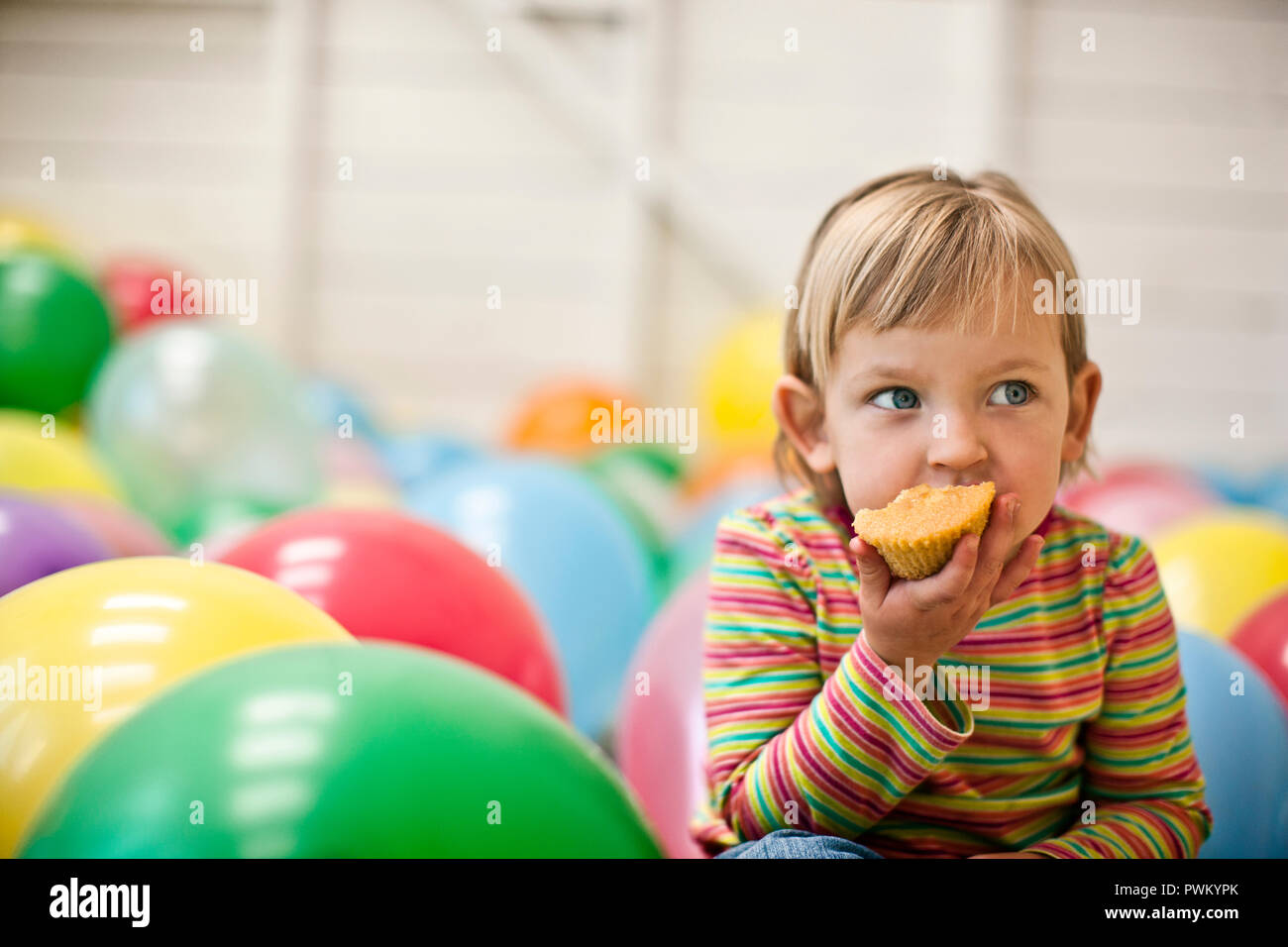 Little girl sitting in a room full of balloons and eating a cupcake. Stock Photo