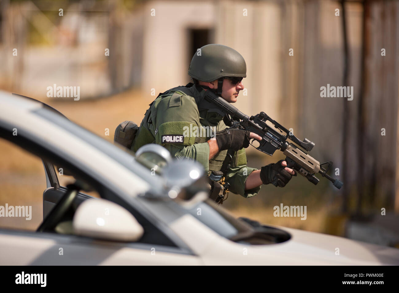 Male police officer holding a gun during an exercise at a training facility. - Stock Image