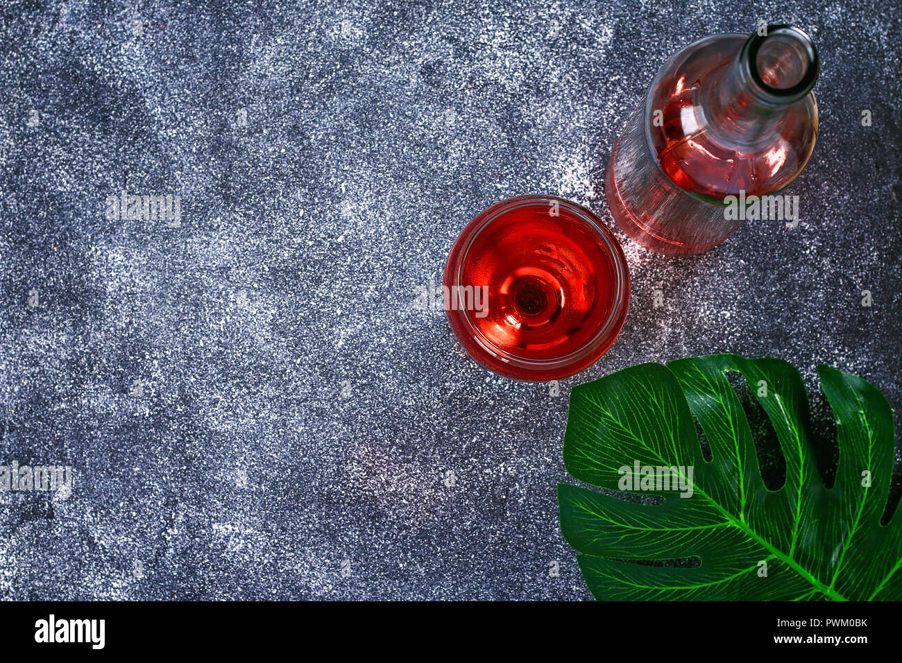Wine in a wineglass, a bottle and a tropical leaf. Top view. Wine drink on a gray background. Copy space Stock Photo