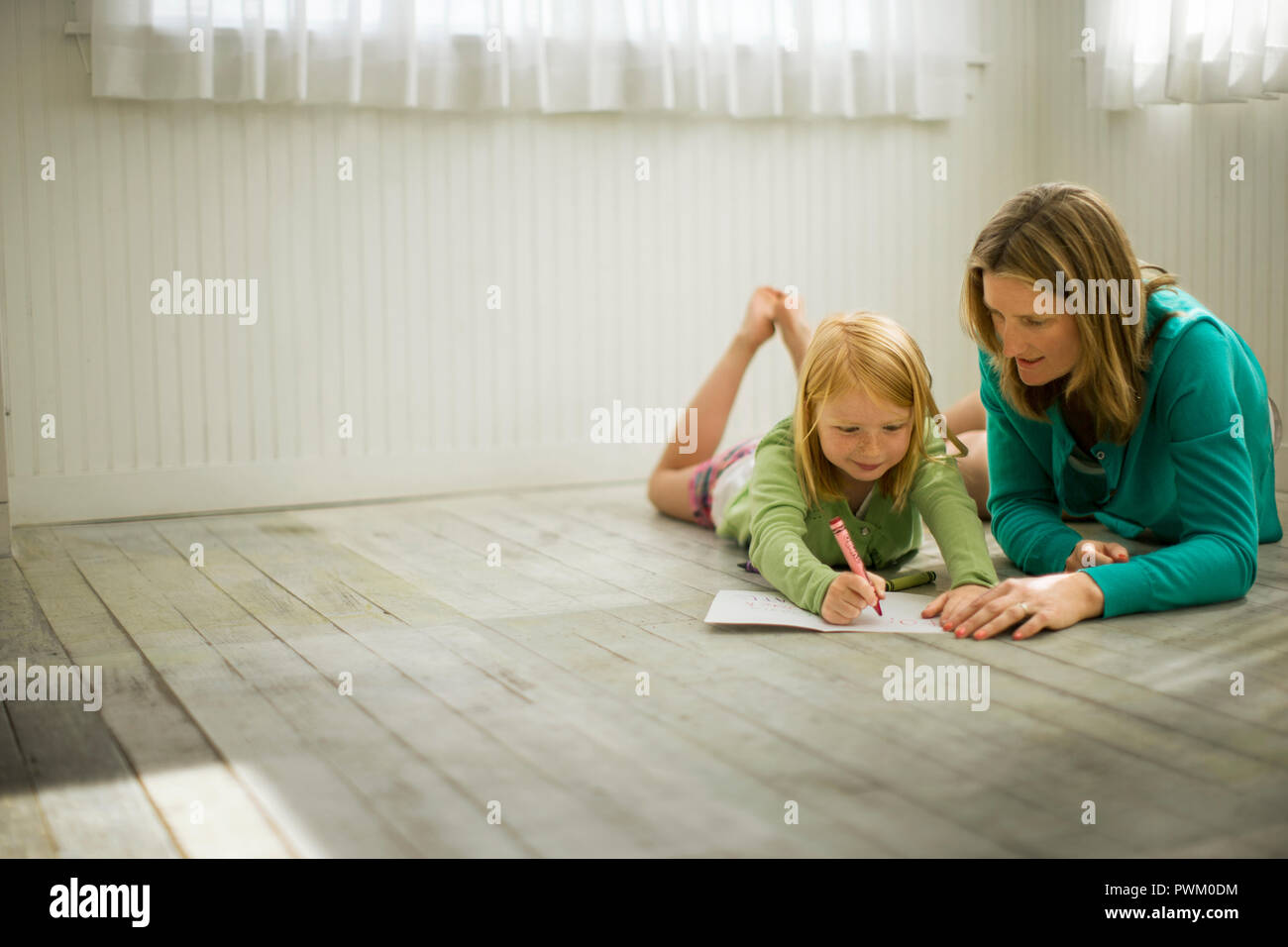 Smiling young girl coloring with her mother. Stock Photo