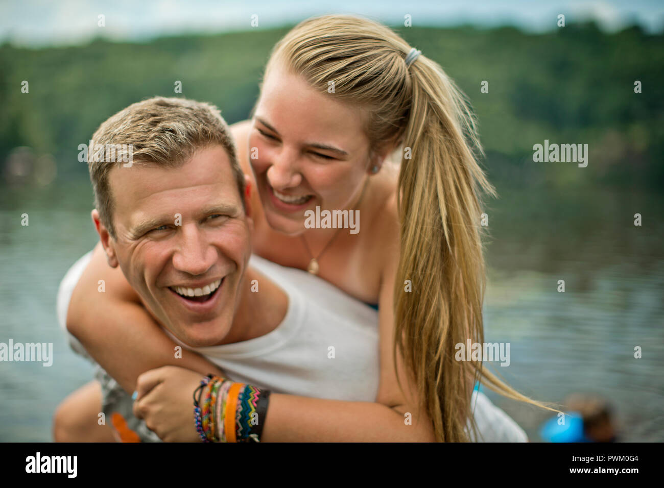 Smiling middle aged man giving his daughter a piggyback ride. Stock Photo