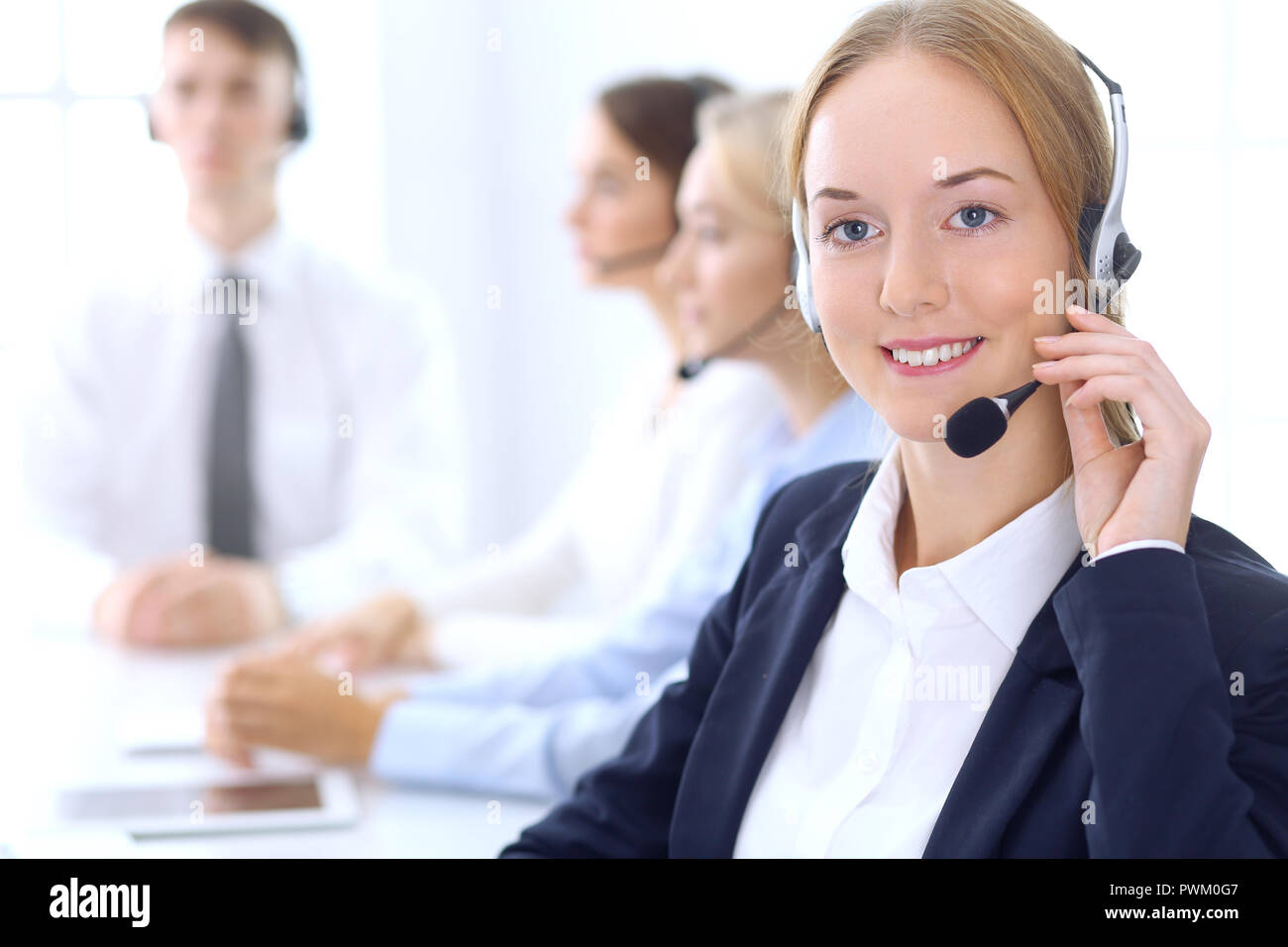Group Of Call Center Operators At Work Focus At Blonde