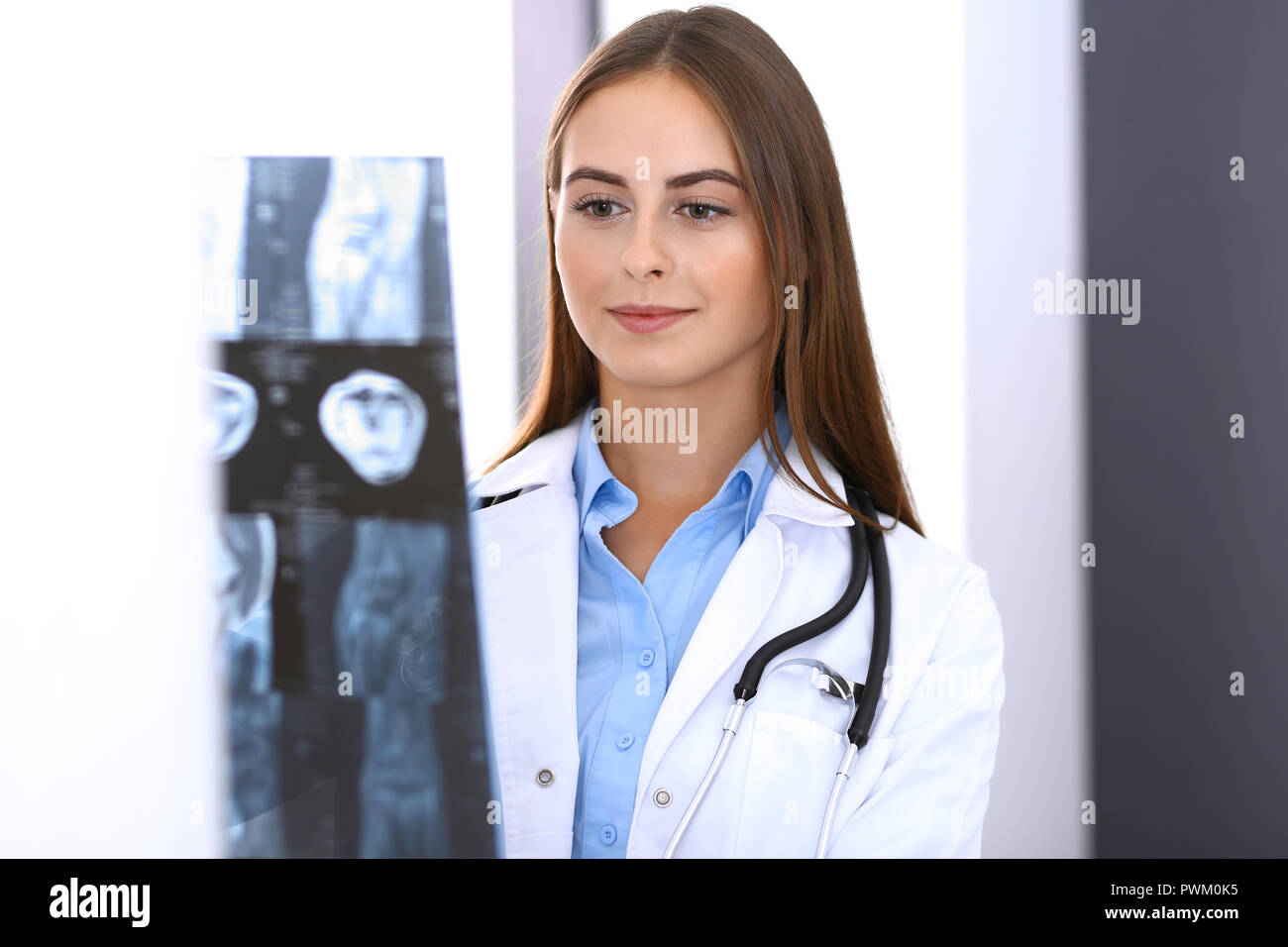 Doctor woman examining x-ray picture while standing near window in hospital. Surgeon or orthopedist at work. Medicine and healthcare concept. - Stock Image
