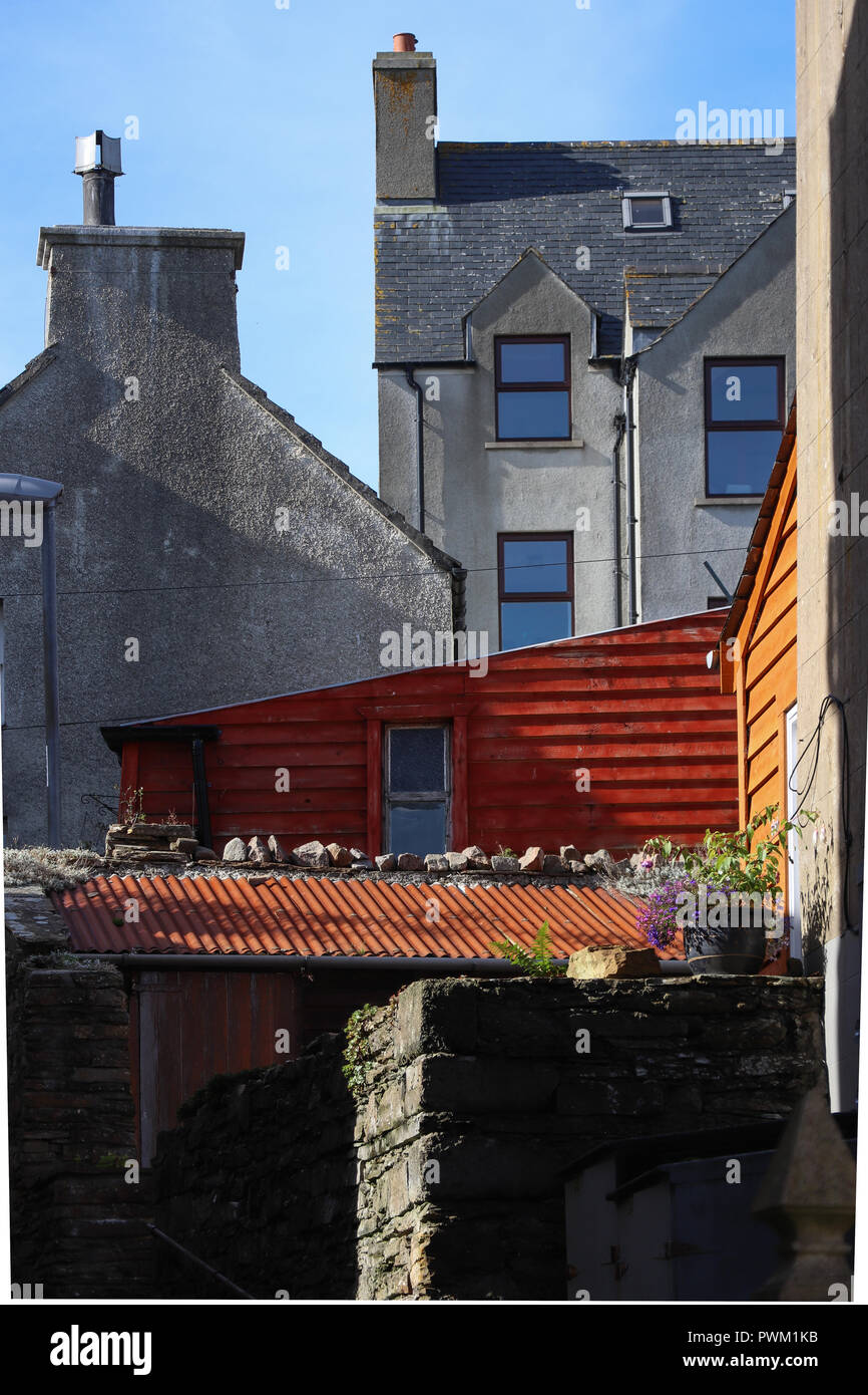Boldly colored red and orange sheds in an otherwise austere Scottish town, Stromness, surprise the unexpecting traveller if he looks up this alley. - Stock Image