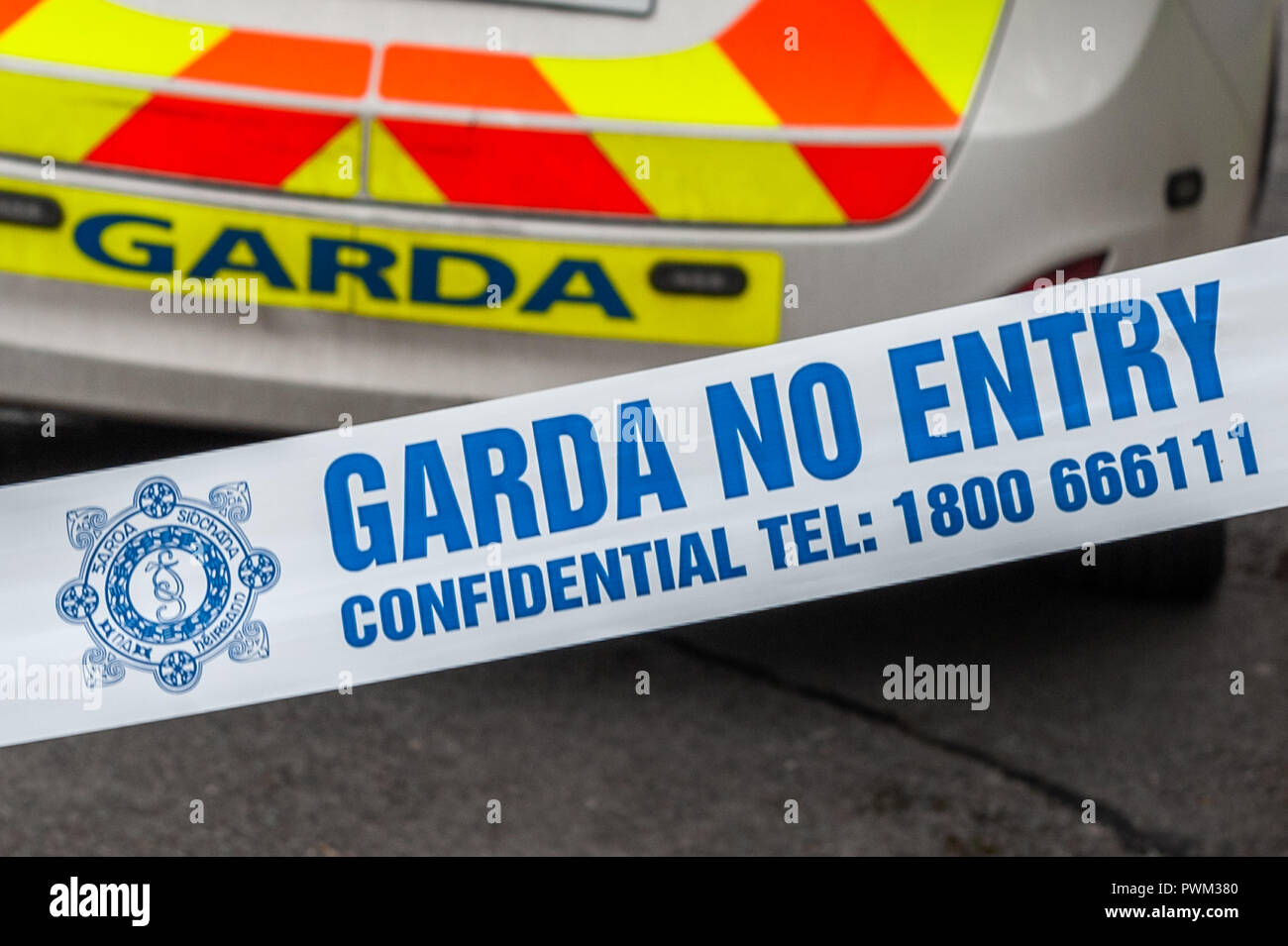 Garda (Irish Police) No Entry tape in front of a Garda Patrol car at an incident in Ireland. - Stock Image
