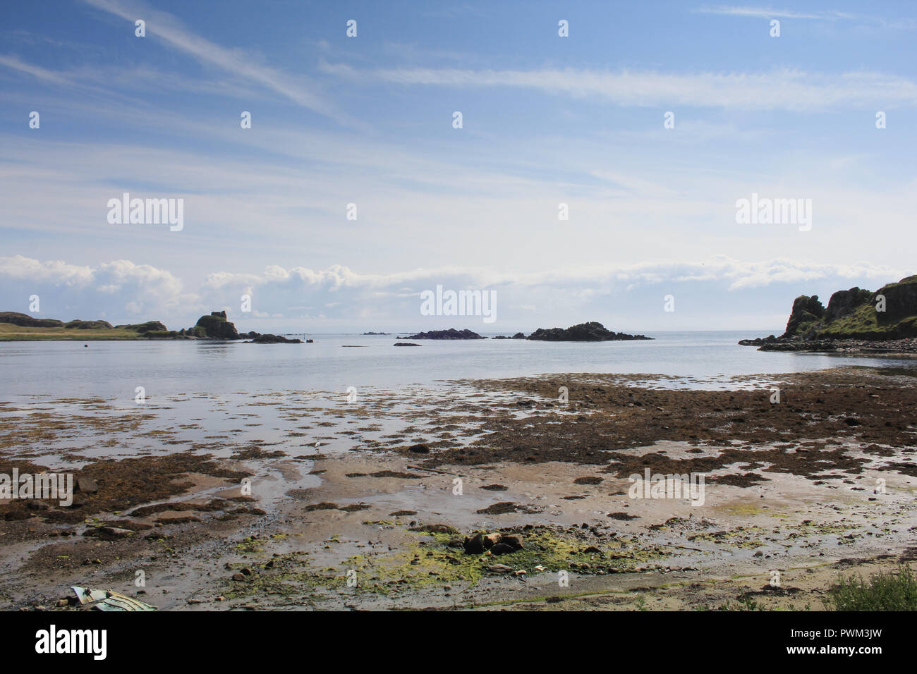 Castle ruins at the seas edge on the scottish Isle of Islay on a lovely summers day. - Stock Image