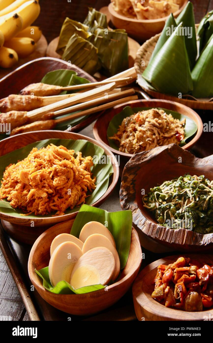 Nasi Jinggo, the Balinese small meal of rice with fried noodles, vegetables, and egg wrapped with banana leaf; served with extra optional side dishes. - Stock Image