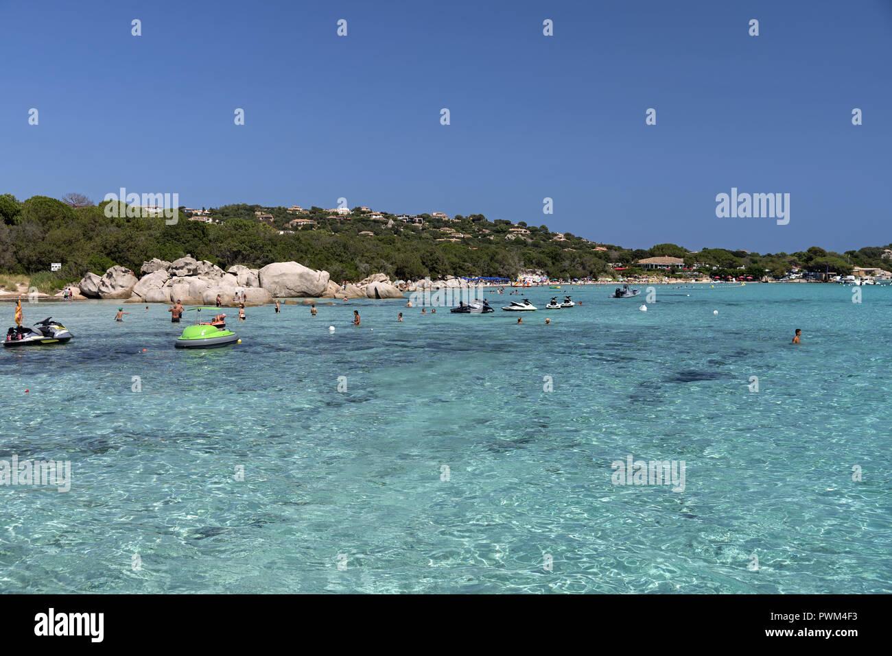 People relaxing on the beach and in the water. Beach of Santa Giulia in Corsica. Plaża Santa Giulia na Korsyce. Ludzie wypoczywający na plaży. - Stock Image
