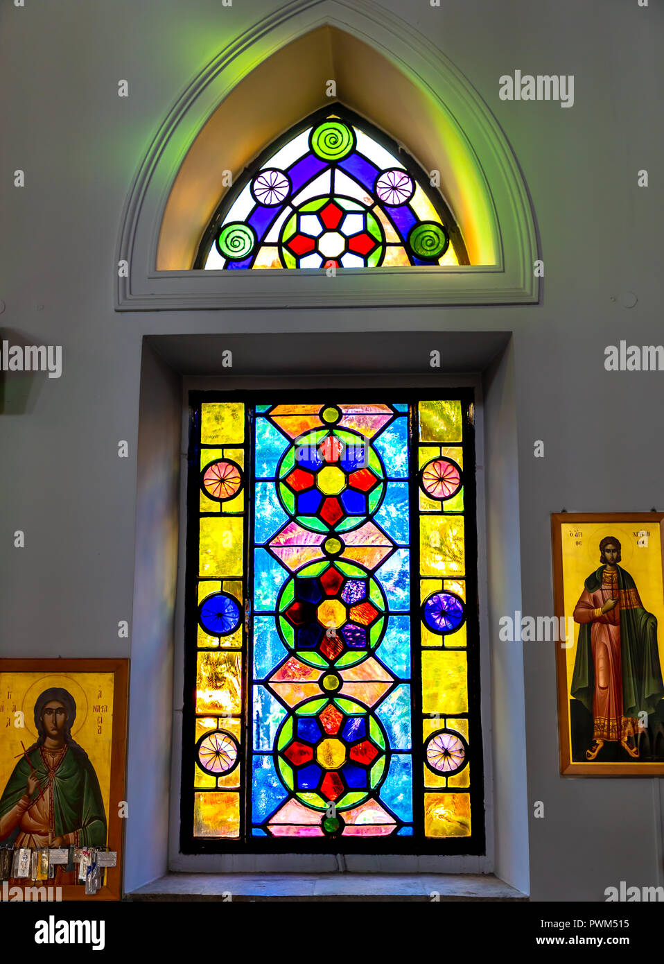 Old stain glass window in an alcove of the Church of Saint Titus. - Stock Image