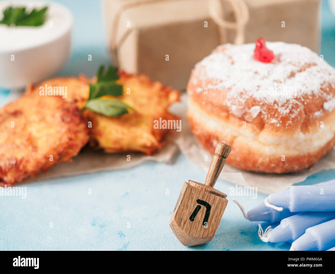 Jewish holiday Hanukkah concept and background. Hanukkah food doughnuts and potatoes pancakes latkes, giftbox, candle and traditional spinnig dreidl on blue background. Copy space for text. - Stock Image