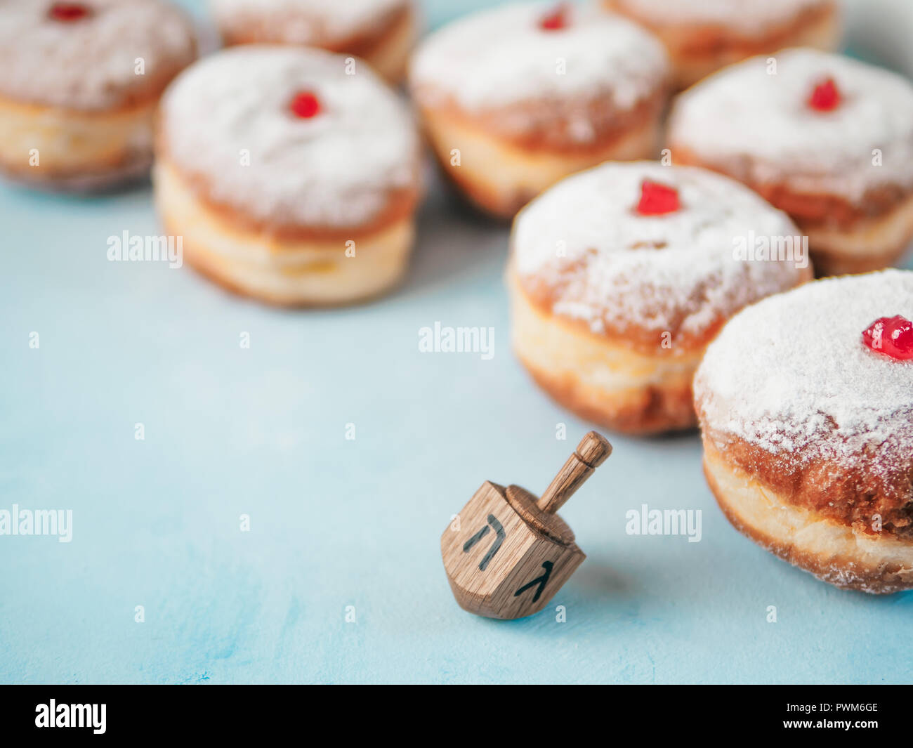 Jewish holiday Hanukkah concept and background. Hanukkah food doughnuts and traditional spinnig dreidl or dredel on blue background. Copy space for text. Shallow DOF - Stock Image