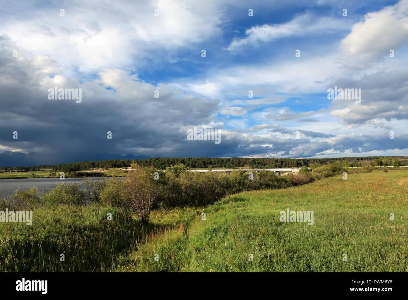 Movement of clouds on the river Irkut. Irkutsk Oblast, Russia. - Stock Image