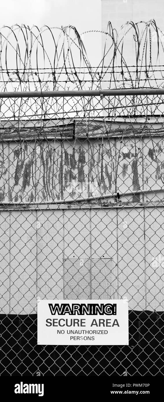 Vertical composition confined area no entry barbed wire fence with razor wire - Stock Image