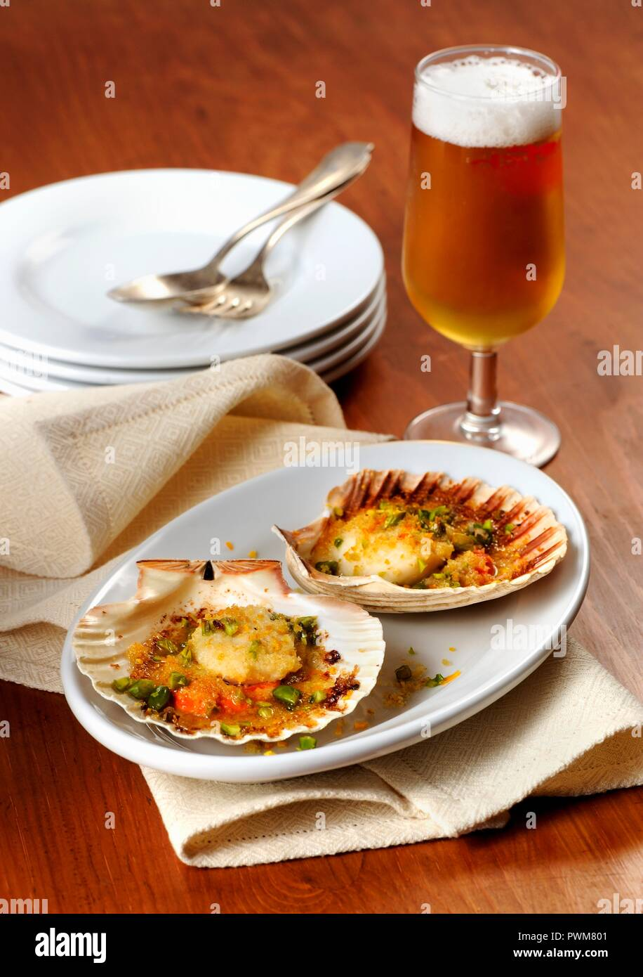 Gratinated scallops and beer - Stock Image