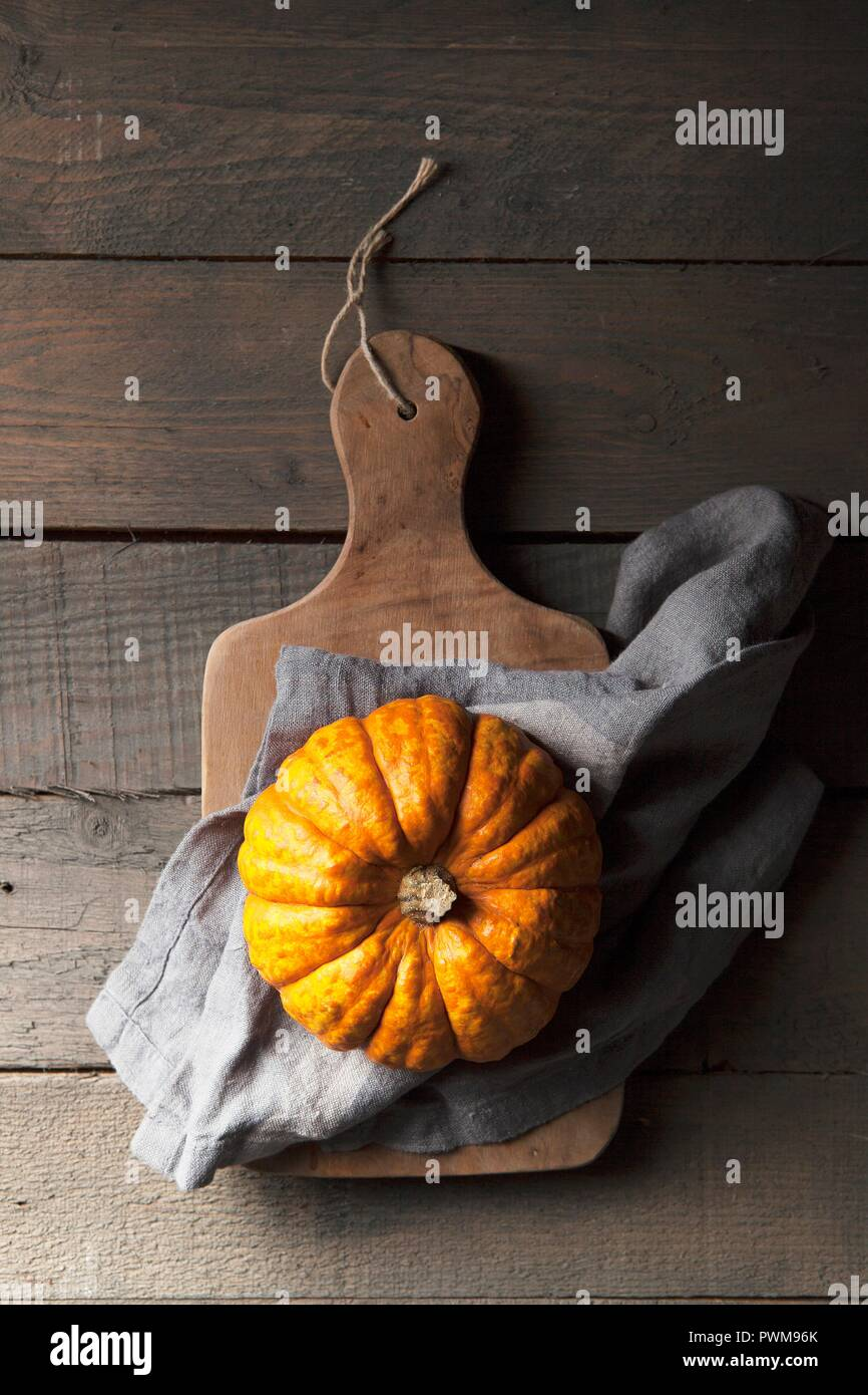 A munchkin pumpkin on a rustic wooden background with a grey linen napkin - Stock Image