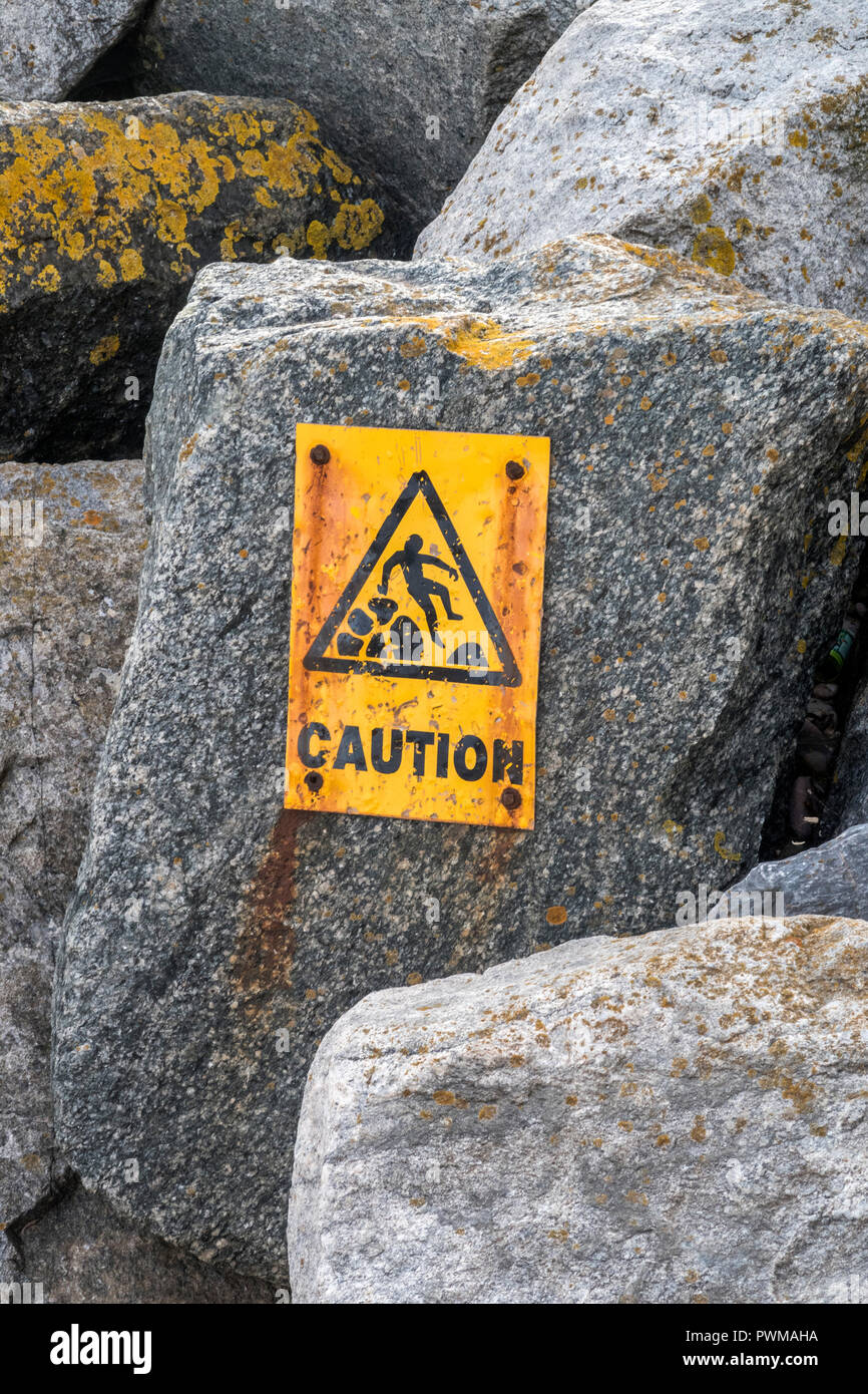 Caution, Slippery rocks sign on rock groynes in Sidmouth, Devon - Stock Image