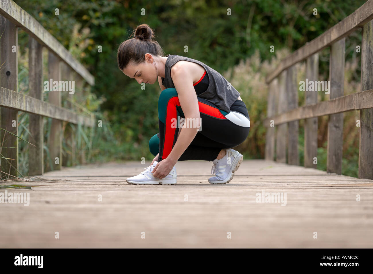 sporty woman tying up her trainers before exercise and running - Stock Image