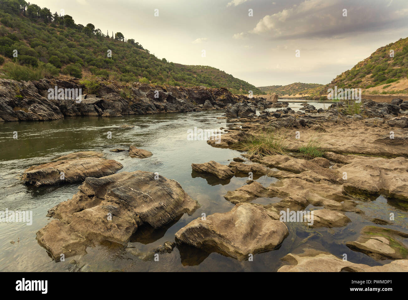 Course of the Guadiana River with its calm waters between the mountains and the rocks of the riverbed, with the cloudy sky in the background - Stock Image
