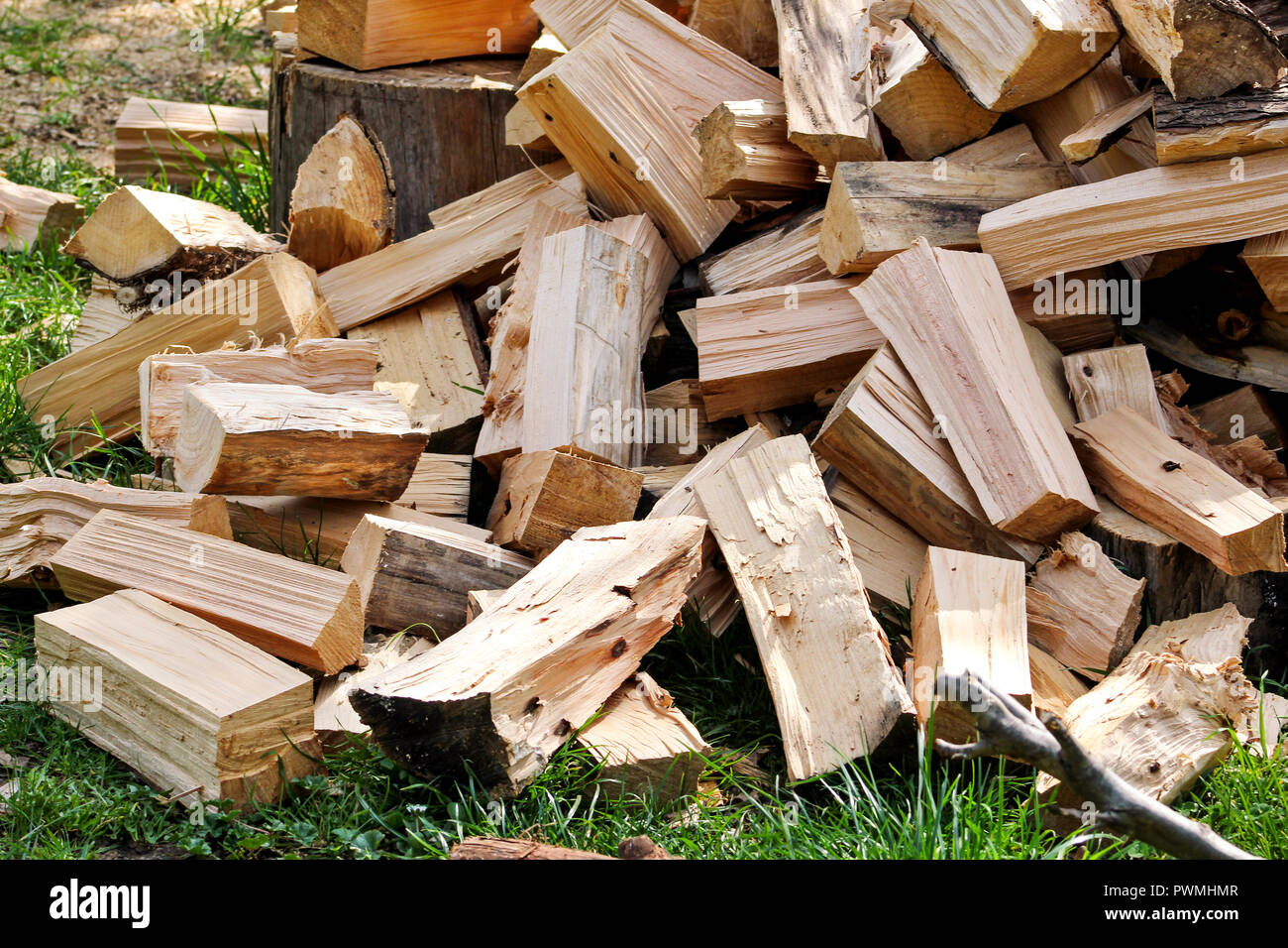 A pile of chopped firewood logs ready for the winter. Cut logs fire wood. Hardwood, wood and lumber industry. Heating season, winter season. Renewable Stock Photo