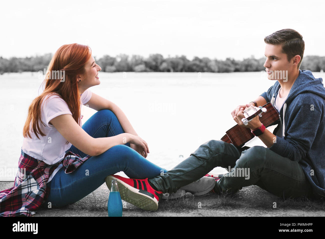 Couple of happy beaming teenagers enjoying nice evening with guitar near the river - Stock Image