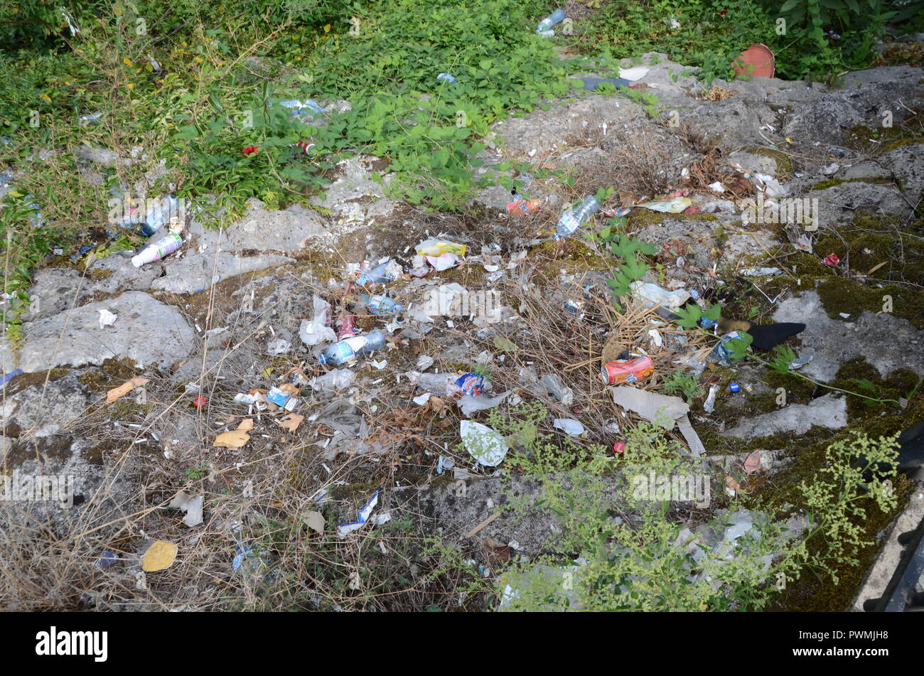 a pile of litter near lake skadar montenegro with cans and bottles and plastic bags etc - Stock Image