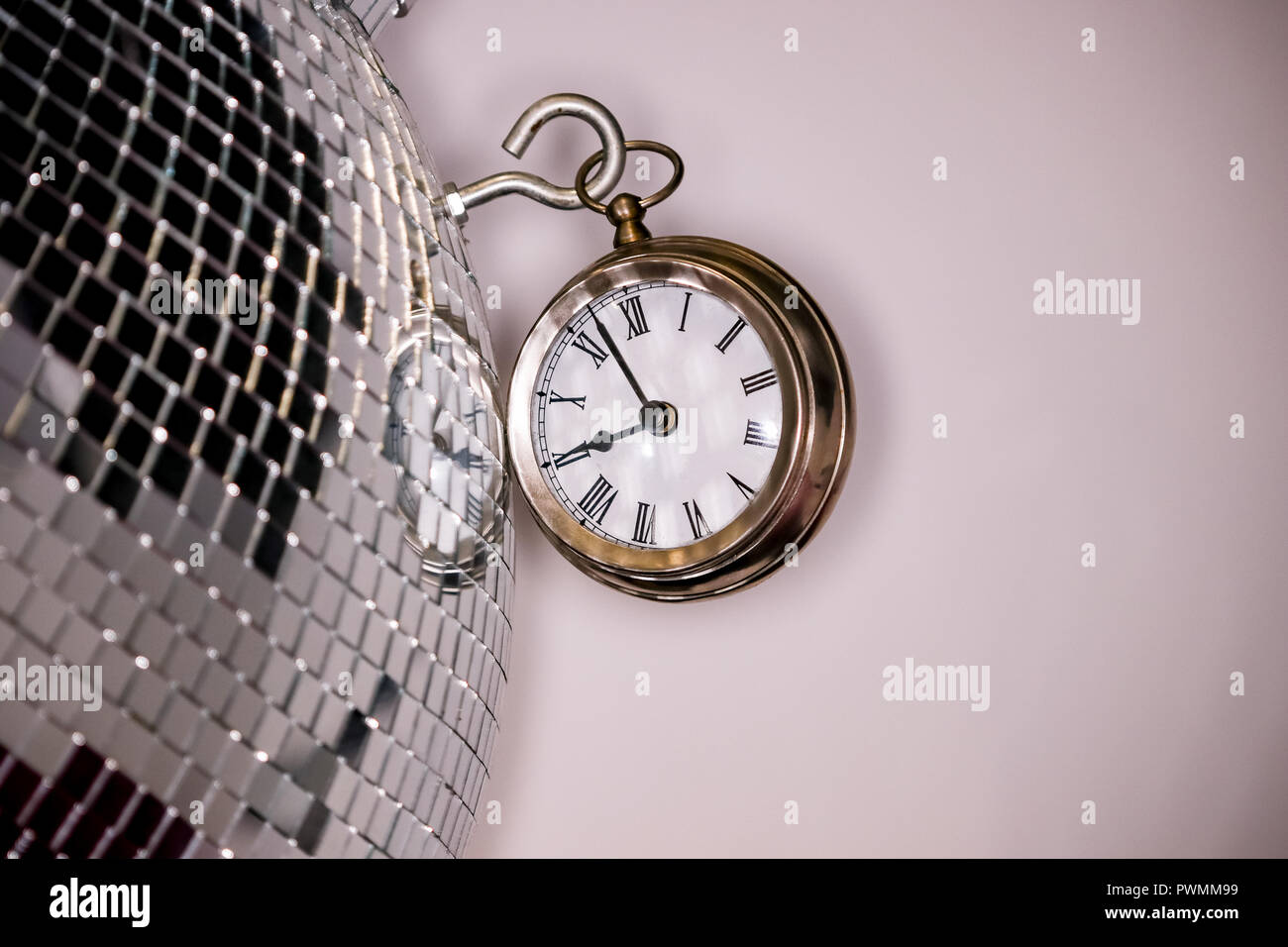 Arty shot of a metal large pocket watch clock next to a silver disco ball - Stock Image