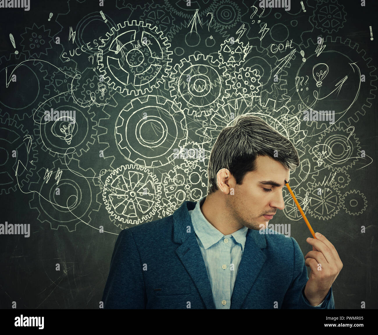 Hard thinking serious man over blackboard background gear brain arrows and mess as thoughts. Concept for mental, psychological development. - Stock Image