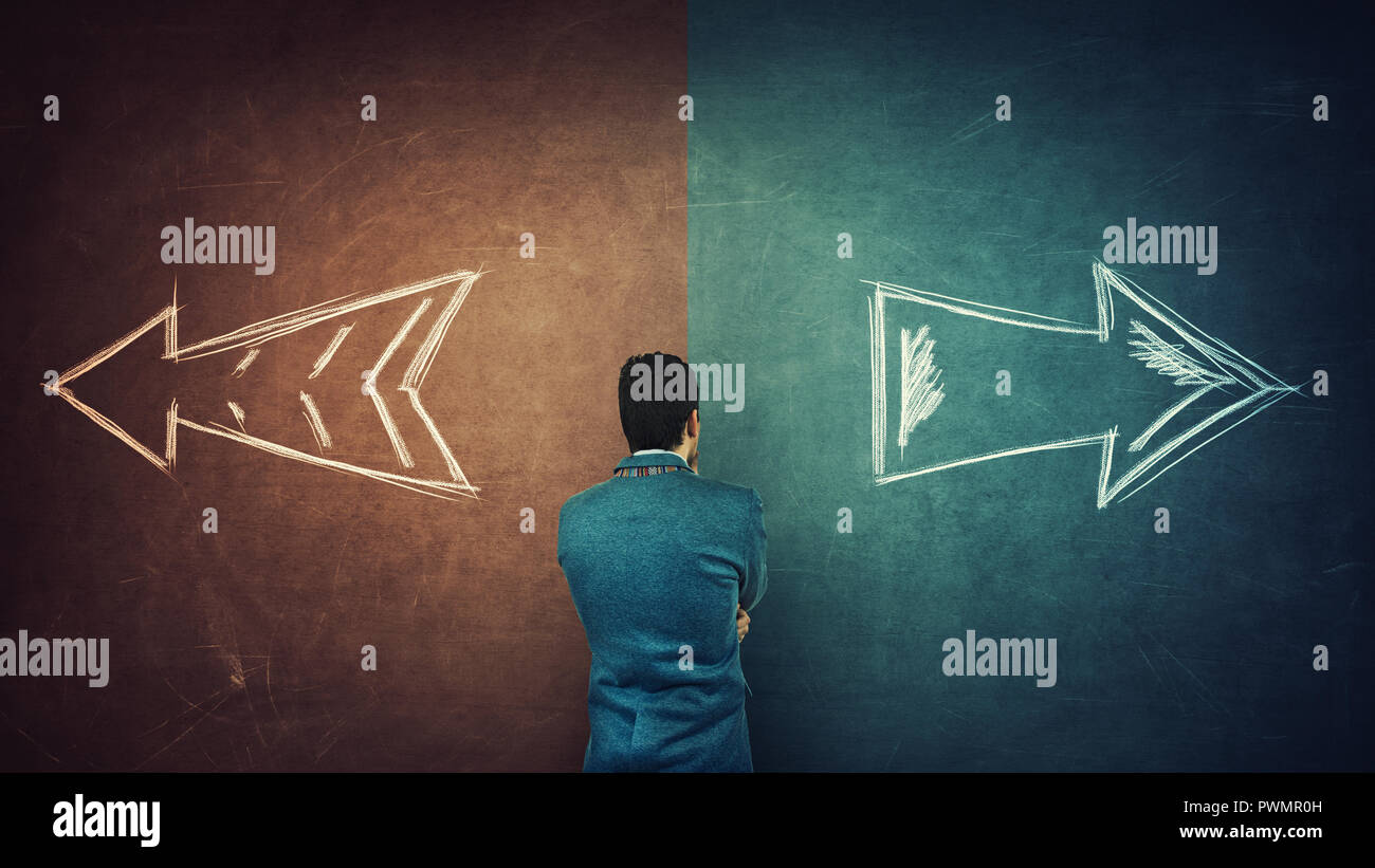 Puzzled businessman and a split blackboard with arrows going in two different ways red and blue side. Correct choice between left and right, failure o - Stock Image