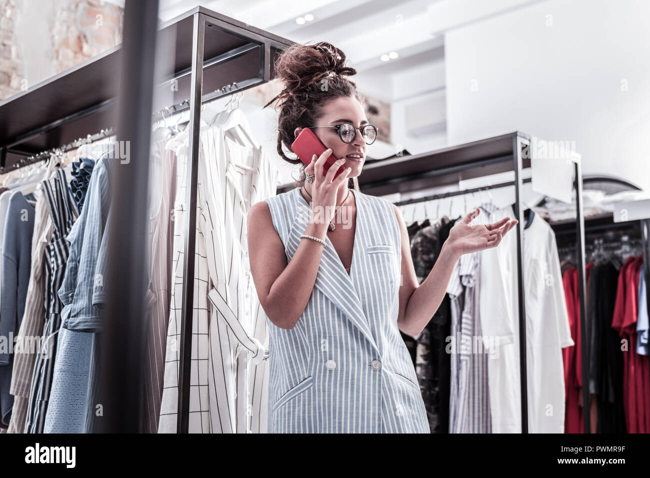 Dark-haired designer wearing striped blue vest speaking by the phone - Stock Image