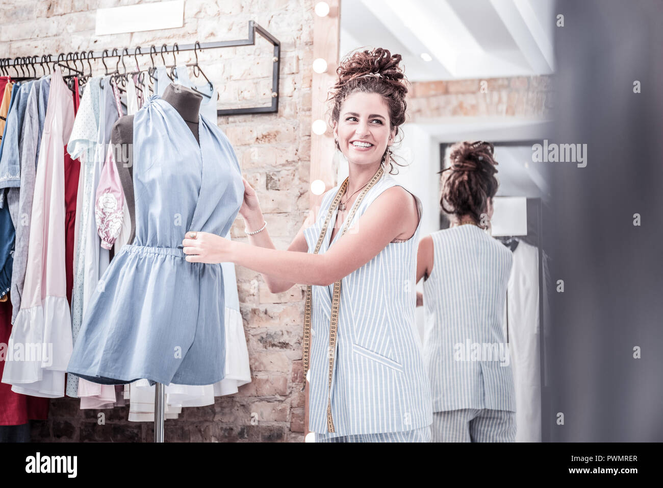 Beaming fashion designer trying her new blue summer jumpsuit on body form - Stock Image
