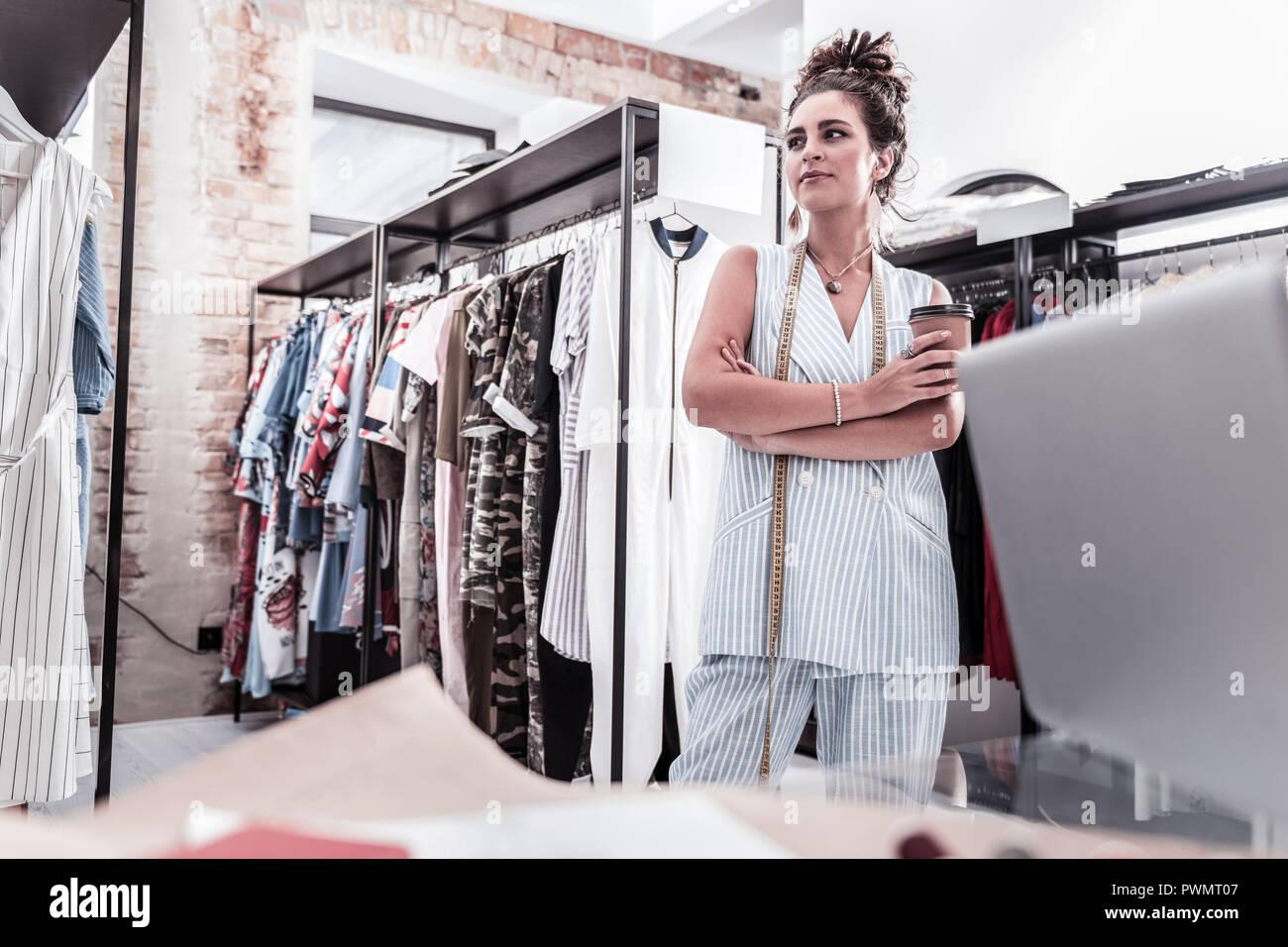 Hard-working creative fashion designer having little coffee break working hard - Stock Image