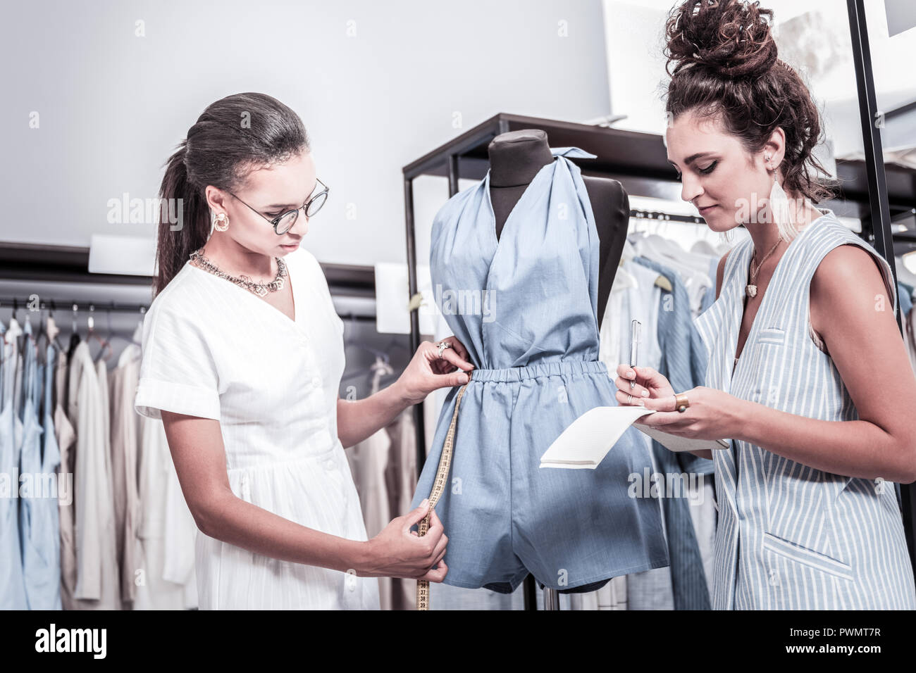 Two creative art students feeling busy while tailoring jumpsuit for their project - Stock Image