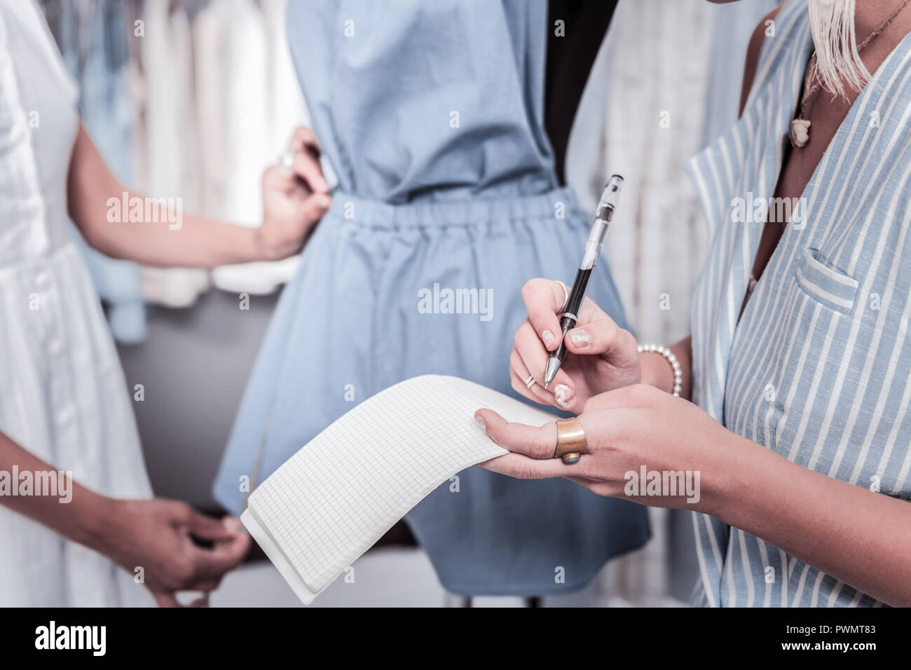 Fashion designer wearing striped vest and nice accessories making some notes - Stock Image