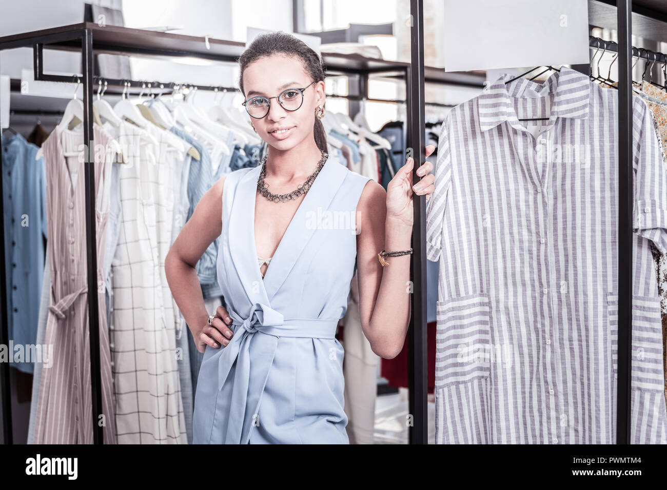Owner of showroom feeling satisfied after presenting summer range of clothes - Stock Image