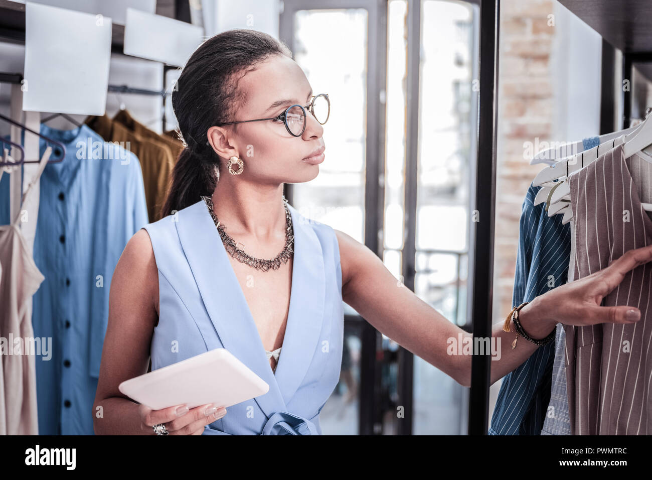 Owner of boutique holding tablet while filling information about size range - Stock Image