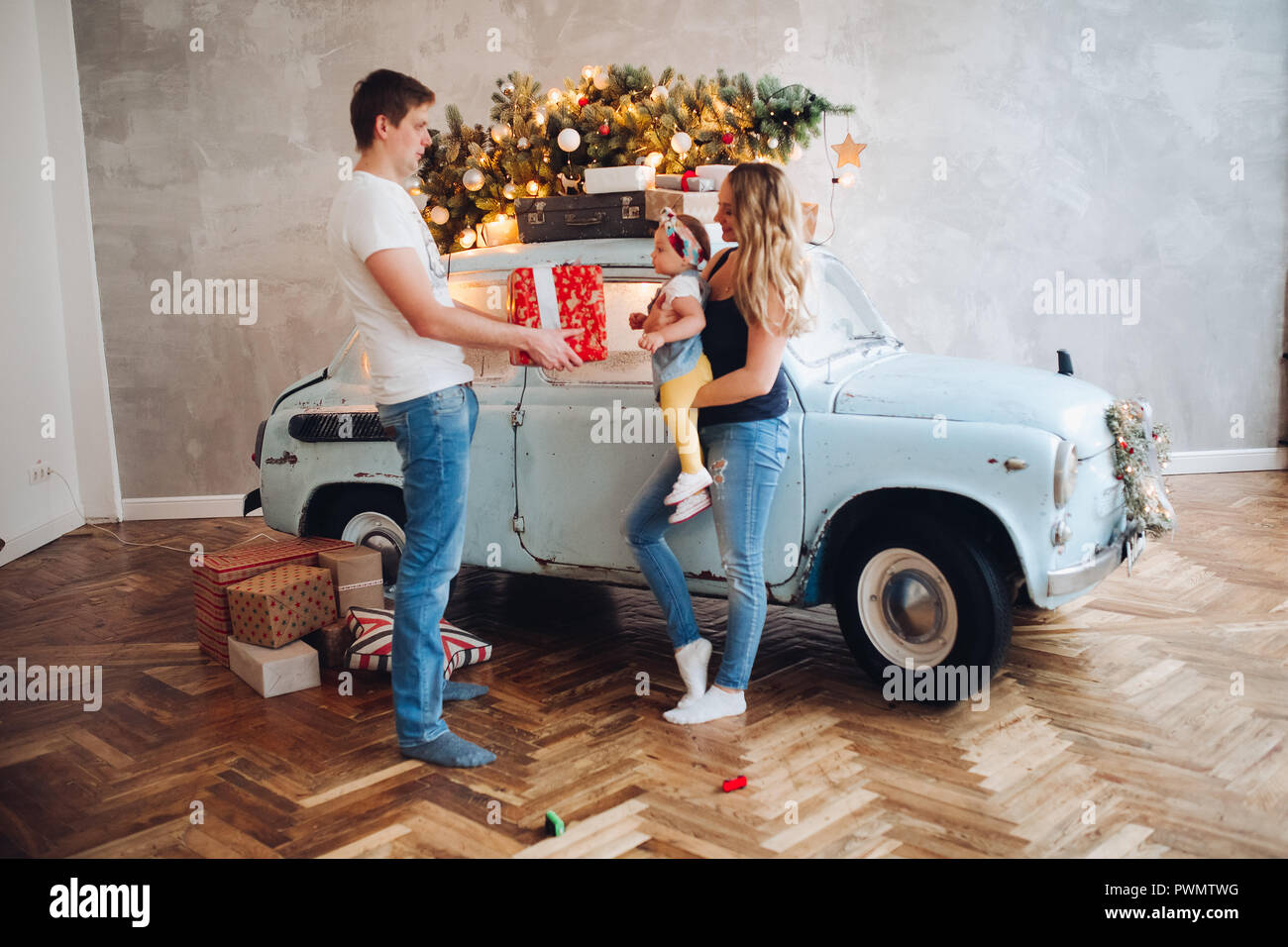 lovely daddy giving christmas present big red box for blonde mom and little cute daughter