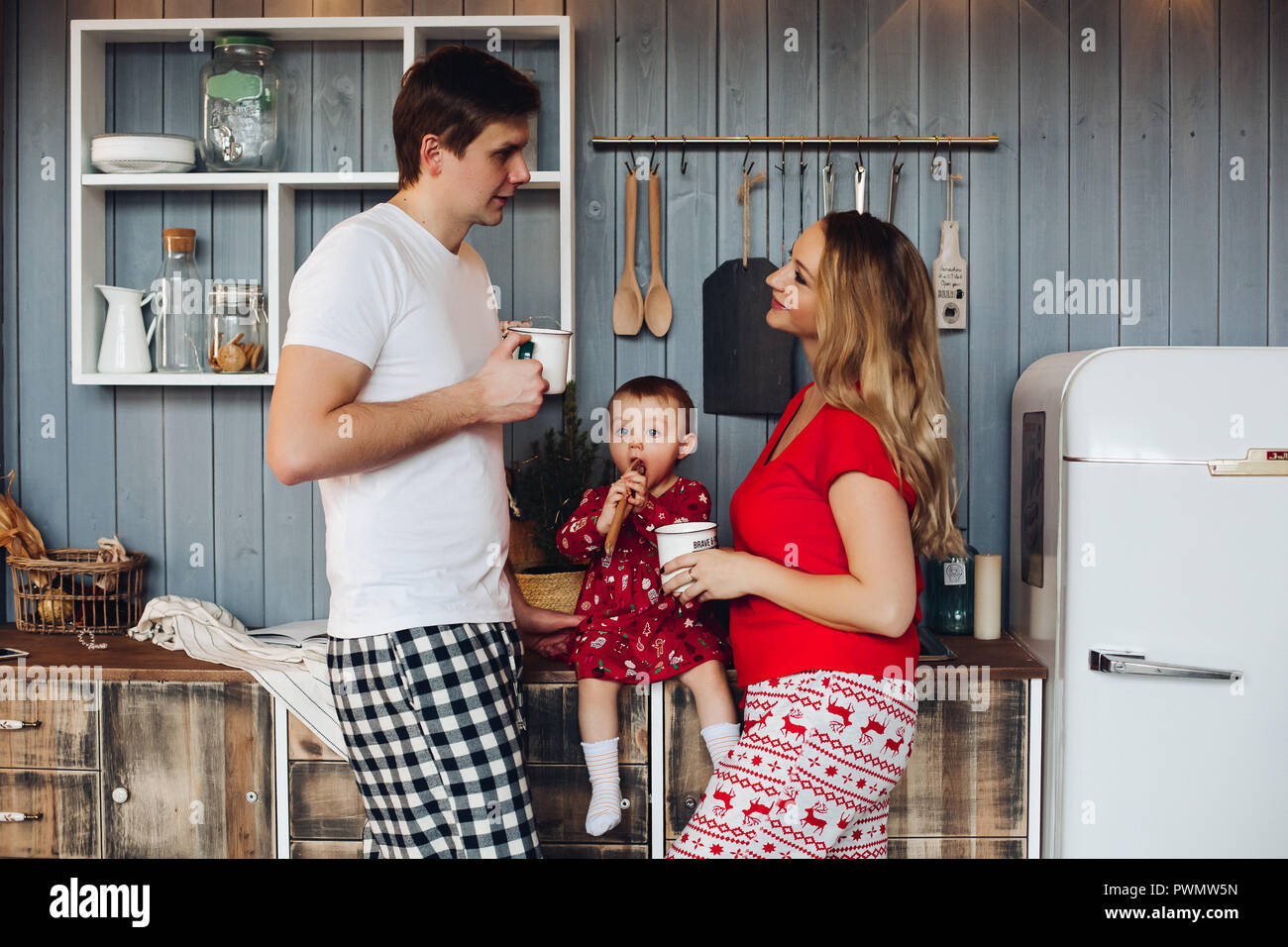 ba709ae9ce Happy family wearing Christmas pajamas cooking together on stylish wooden  kitchen with little daughter. Beautiful